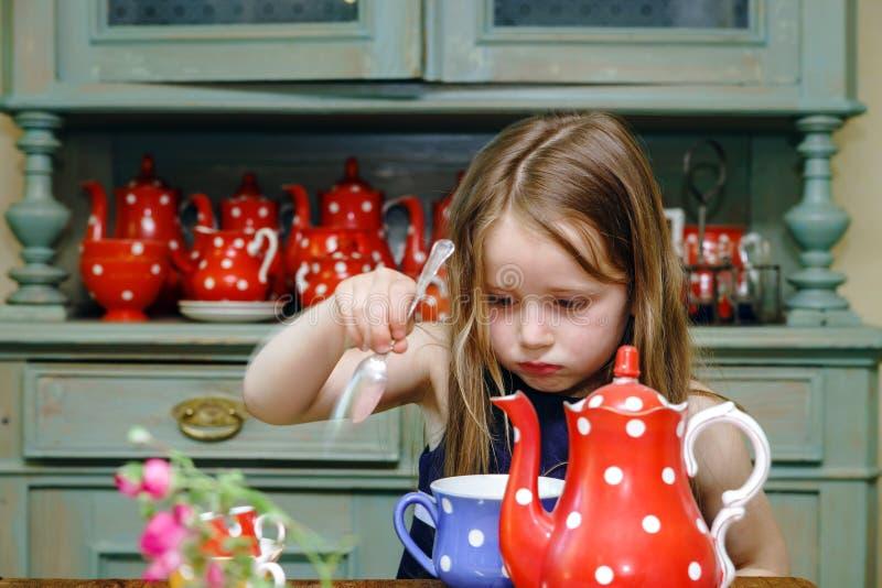 Gullig liten flicka som förbereder te i tekanna royaltyfri bild
