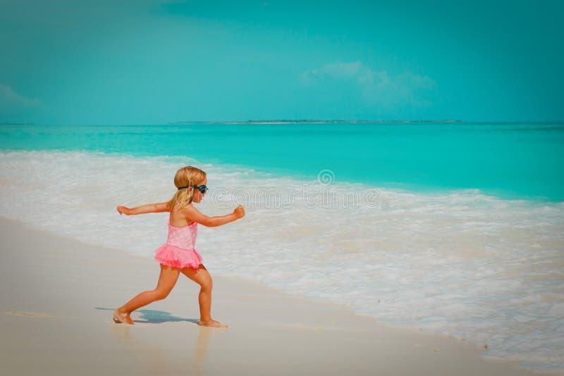 Gullig liten flicka som går att simma på stranden royaltyfri fotografi