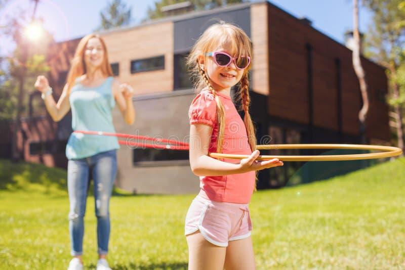 Gullig liten flicka som gör hula-beslaget i bakgården royaltyfria foton
