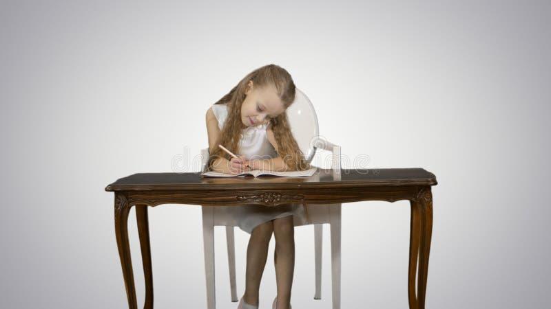 Gullig liten flicka som gör läxa som ner skriver på vit bakgrund royaltyfri foto