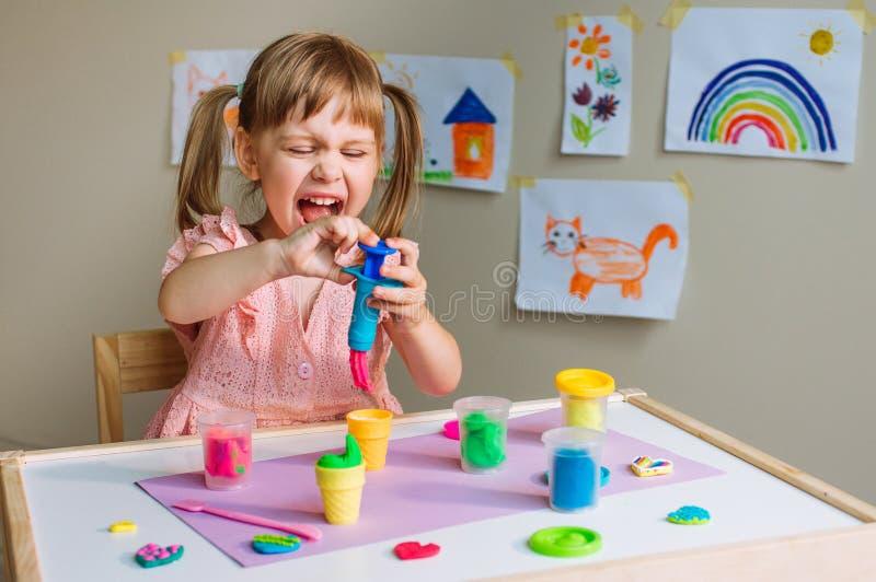 Gullig liten flicka som gör leksakglass från färgrik lera royaltyfria bilder
