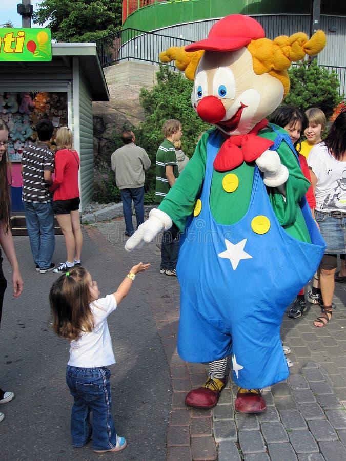 Gullig liten flicka som hälsar en clown royaltyfria foton