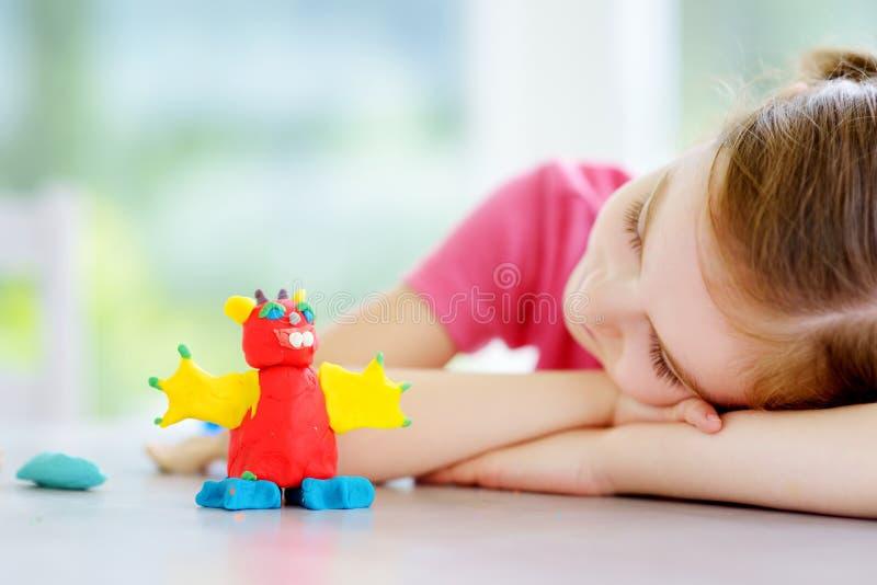 Gullig liten flicka som har gyckel med att modellera lera på en daycare Idérik unge som hemma gjuter arkivbilder