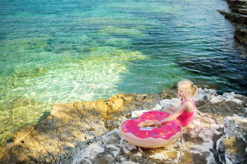 Gullig liten flicka som har gyckel på den Emplisi stranden, pittoresk stenig strand i en avskild fjärd, med klart vatten som är p arkivfoto
