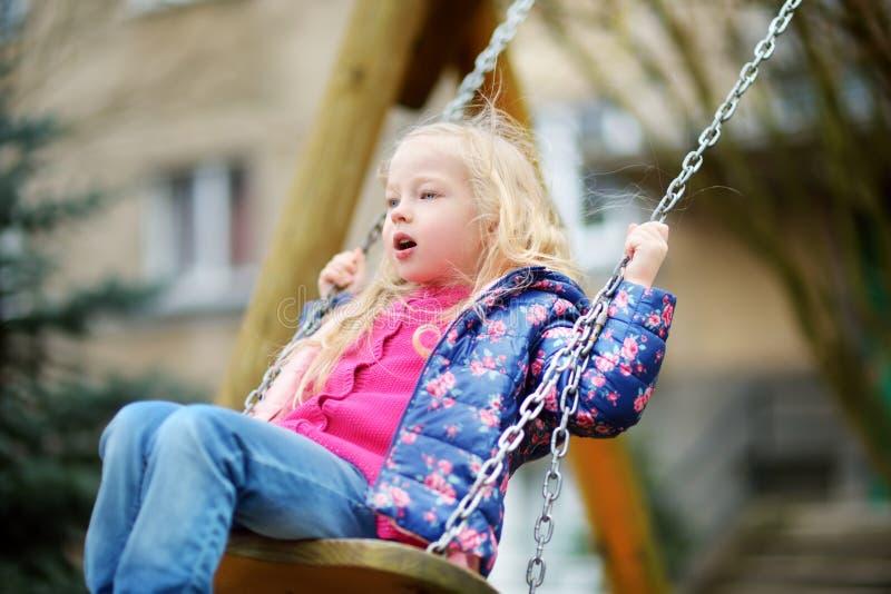 Gullig liten flicka som har gyckel på en gunga på härlig vårdag arkivfoton