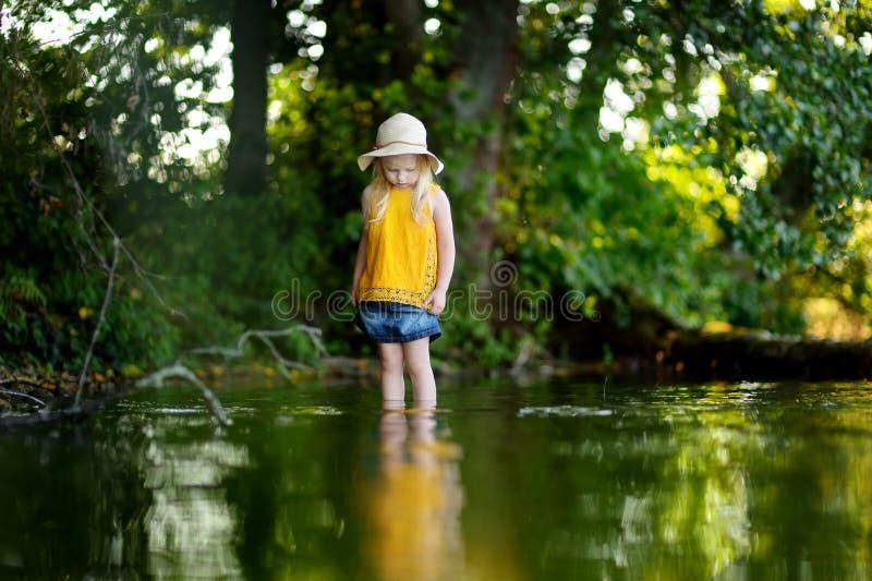 Gullig liten flicka som har gyckel vid en flod på solig sommardag royaltyfri foto