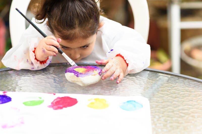 Gullig liten flicka som har roligt och att färga med borsten, att spela och att måla Förskolebarn med målarfärg på trädgården royaltyfria bilder