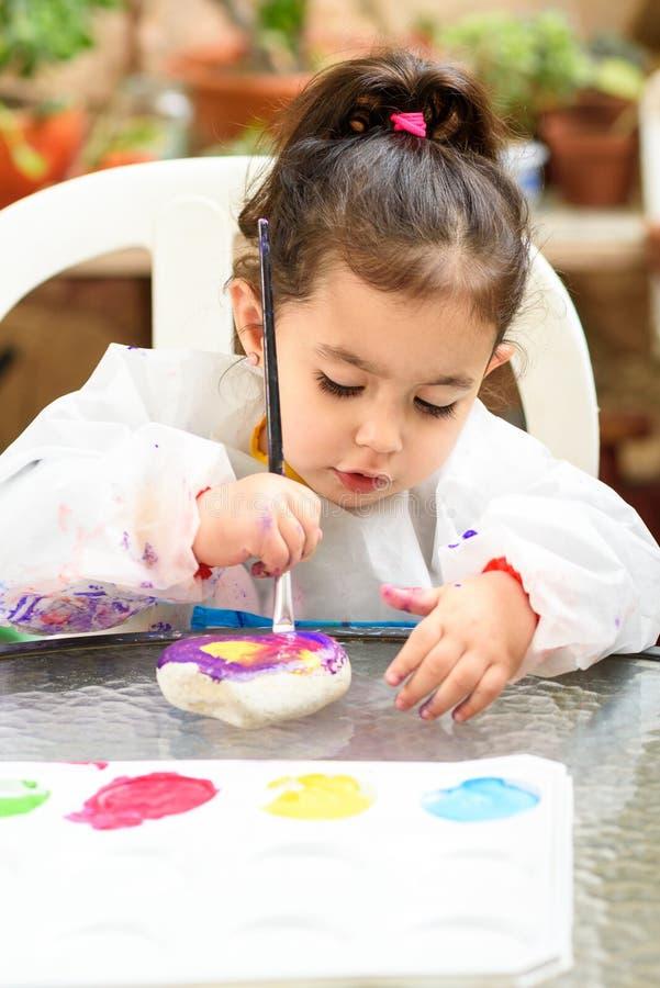 Gullig liten flicka som har roligt och att färga med borsten, att spela och att måla Förskolebarn med målarfärg på trädgården arkivfoton