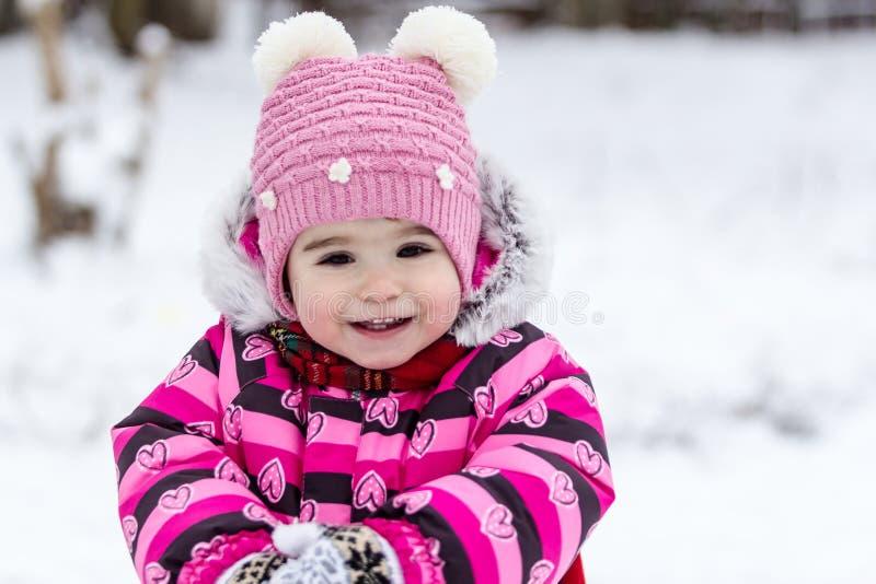 Gullig liten flicka som har roligt utomhus- på naturen på vintern arkivfoton