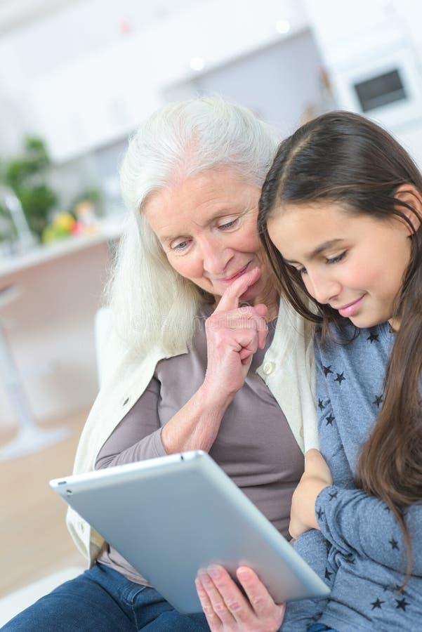 Gullig liten flicka som hemma använder minnestavlaPC med mormodern arkivfoton