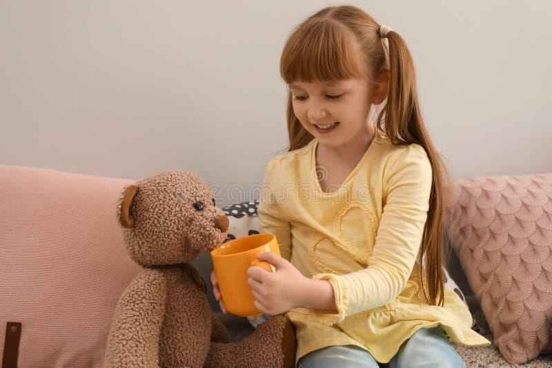 Gullig liten flicka som hemma behandlar leksakbjörnen med koppen av den varma kakaodrinken arkivfoto