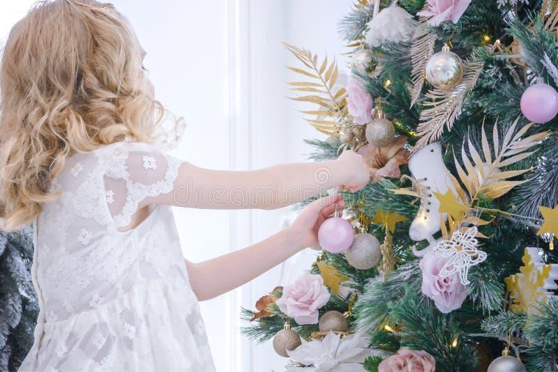 Gullig liten flicka som hemma dekorerar julträdet vid struntsaker royaltyfri foto