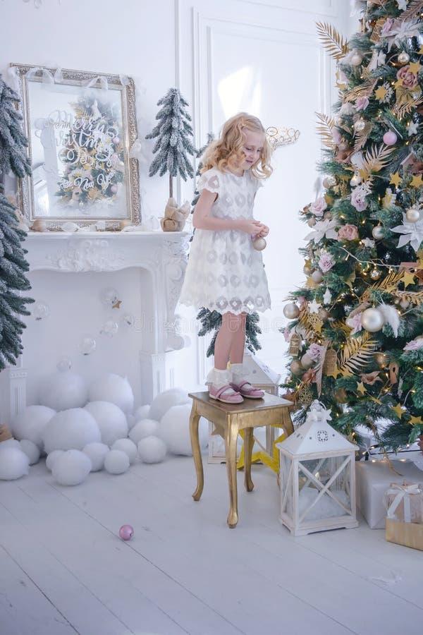 Gullig liten flicka som hemma dekorerar julträdet vid struntsaker arkivfoton