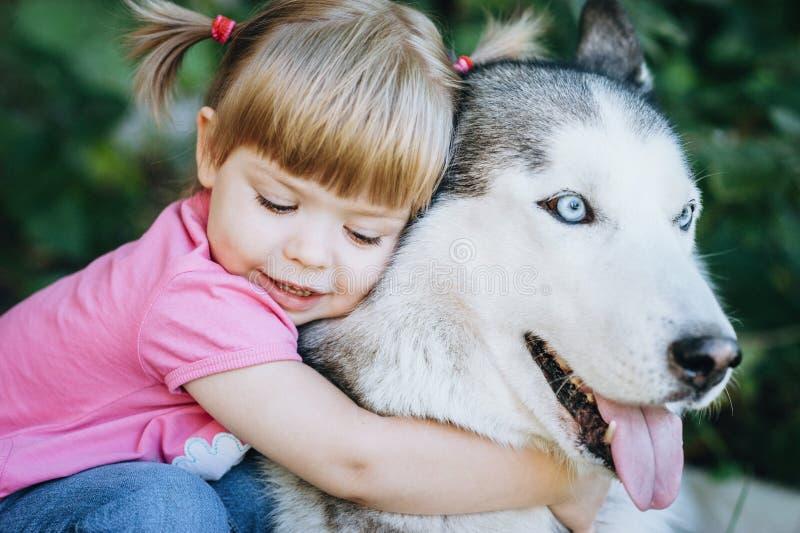 Gullig liten flicka som kramar ett skrovligt royaltyfria bilder