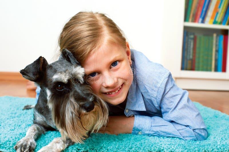 Gullig liten flicka som kramar miniatyrschnauzeren arkivfoto