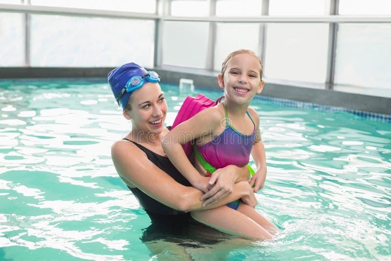 Gullig liten flicka som lär att simma med lagledaren royaltyfria bilder