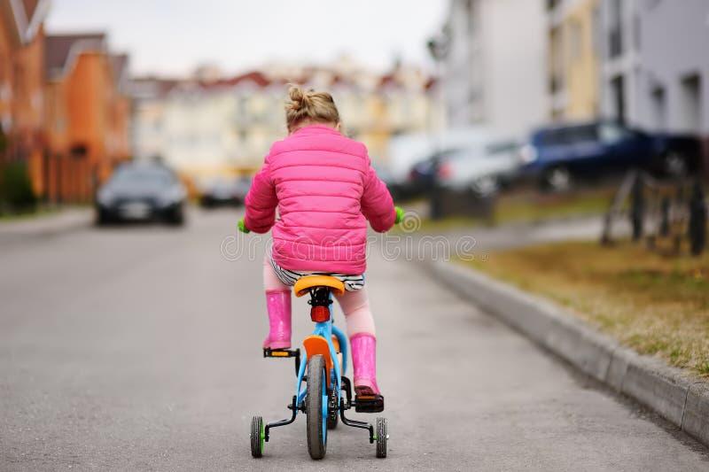 Gullig liten flicka som lär ritt en cykel fotografering för bildbyråer