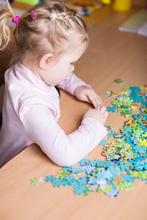 Gullig liten flicka som löser pussel arkivbild