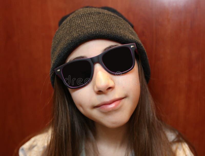 Gullig liten flicka som ler bära vit och svart solglasögon fotografering för bildbyråer