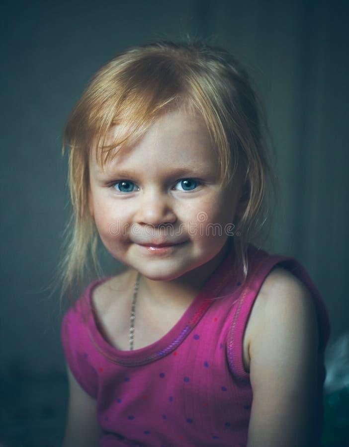 Gullig liten flicka som ler på grå bakgrund royaltyfri fotografi