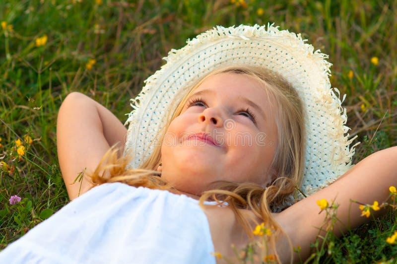 Gullig liten flicka som ligger på ängen och daydreamien arkivbilder