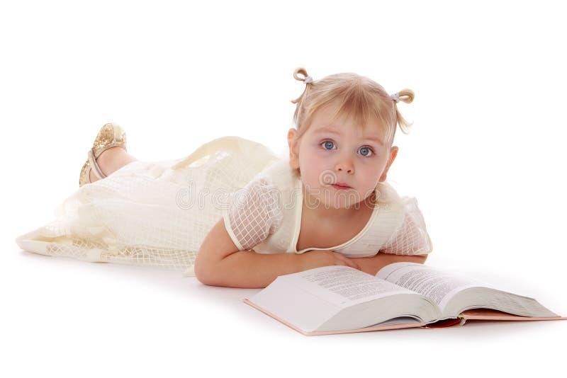 Gullig liten flicka som ligger på golvet och läsningen royaltyfri foto