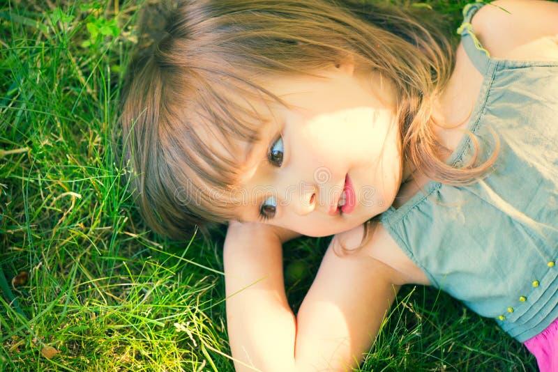 Gullig liten flicka som ligger på grönt gräs arkivbild