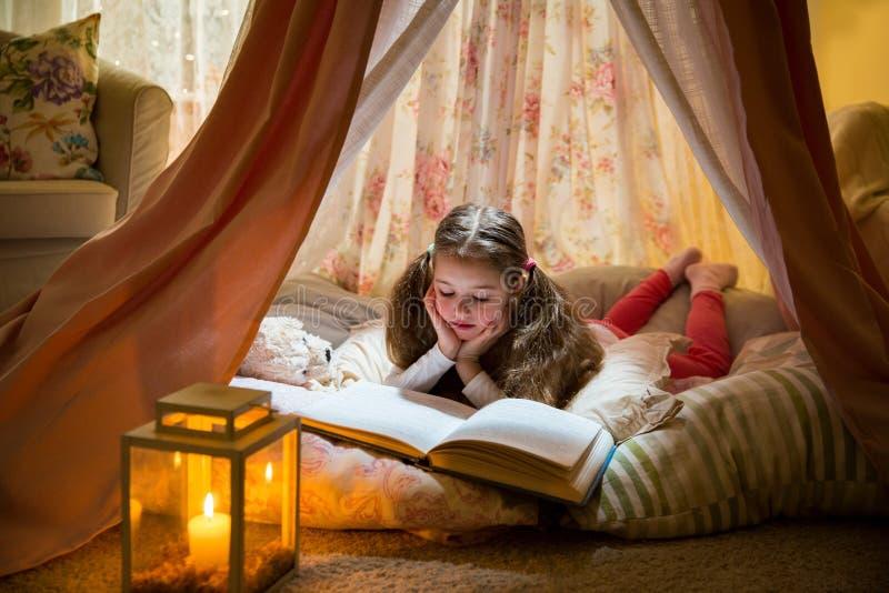 Gullig liten flicka som ligger på kuddar i hemlagat rosa tält med blomman royaltyfri bild