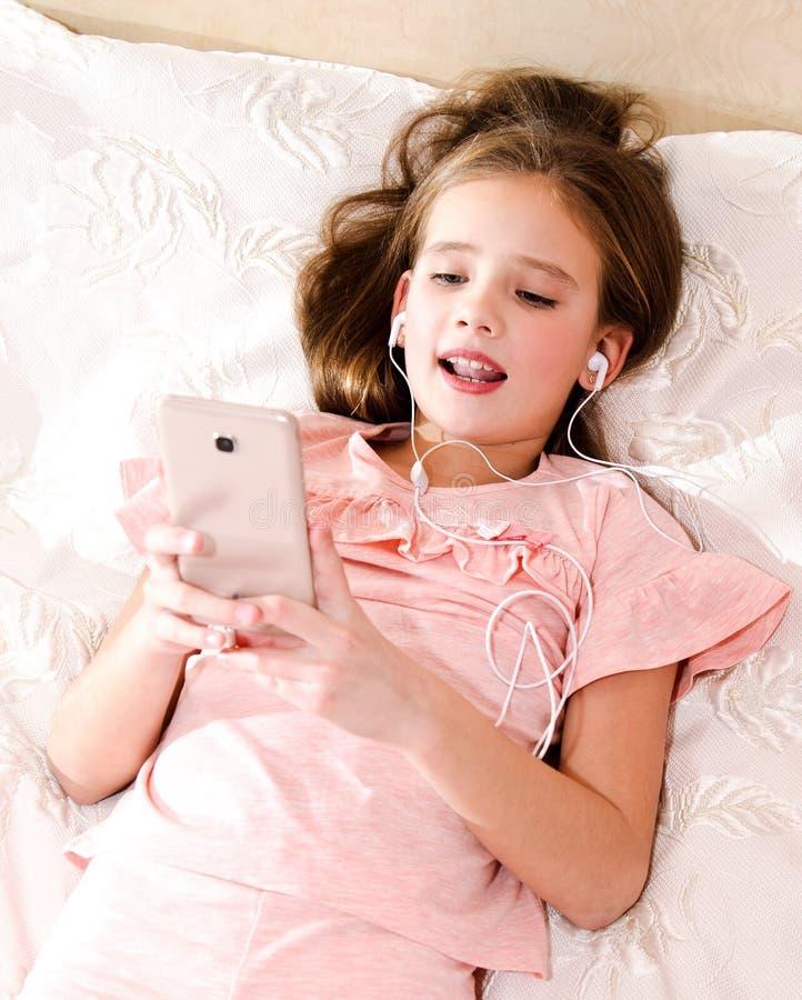 Gullig liten flicka som ligger på sängen som lyssnar till musik och att sjunga royaltyfri bild