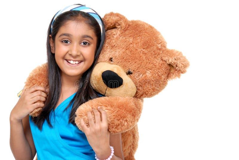 Gullig liten flicka som omfamnar nallebjörnen arkivfoton