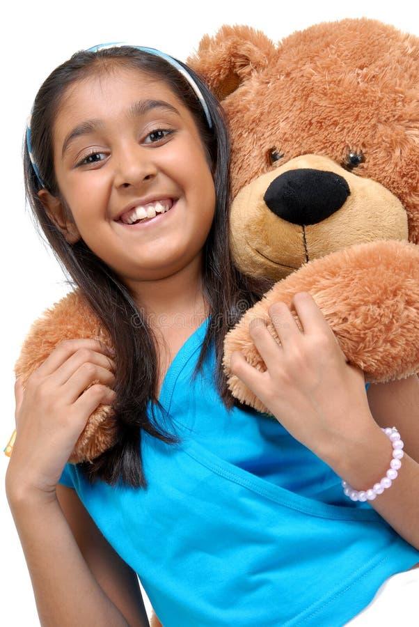 Gullig liten flicka som omfamnar nallebjörnen arkivfoto