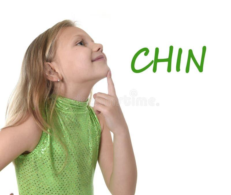 Gullig liten flicka som pekar hennes haka i kroppsdelar som lär engelskaord på skolan arkivbild