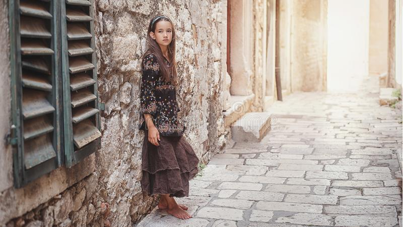 Gullig liten flicka som promenerar den forntida stengatan i den gamla delen av staden fotografering för bildbyråer