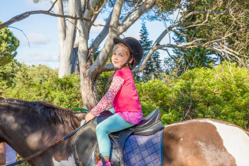 Gullig liten flicka som rider en häst i en skog och ser le royaltyfria foton