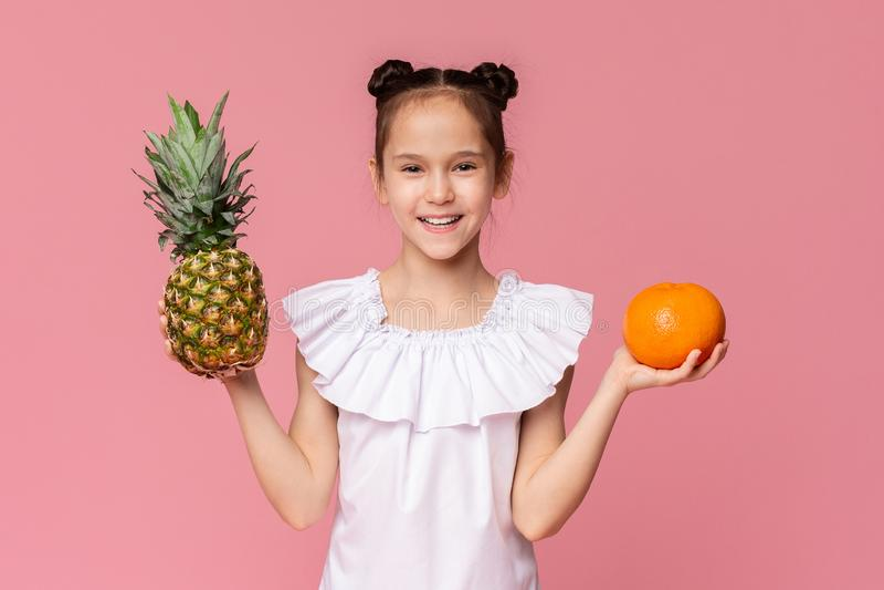 Gullig liten flicka som rymmer den nya ananas och apelsinen arkivbild