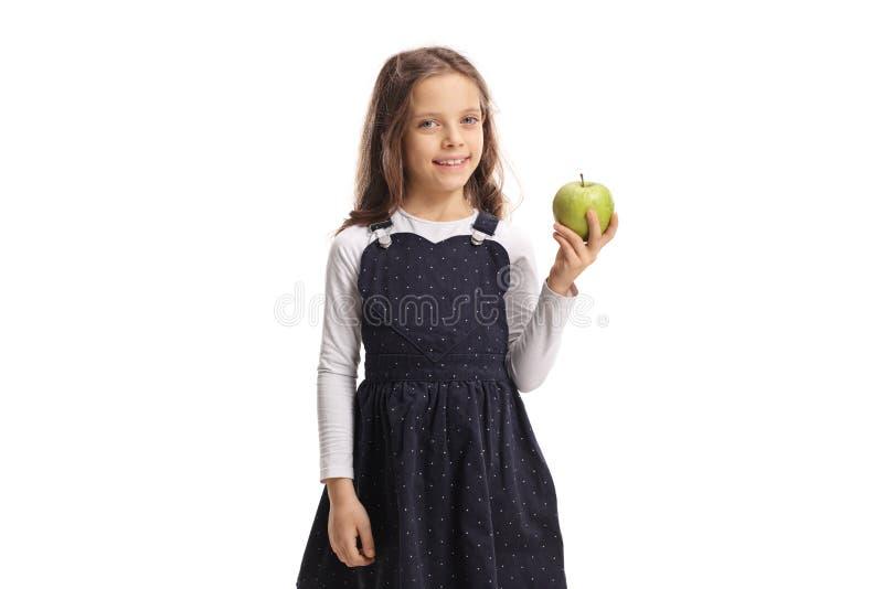 Gullig liten flicka som rymmer ett äpple och le fotografering för bildbyråer