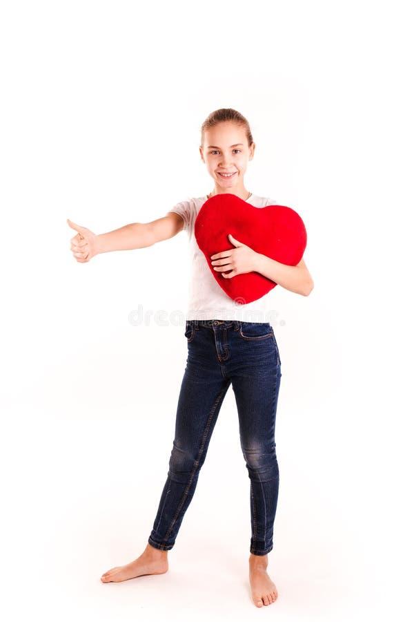 Gullig liten flicka som rymmer röd hjärta isolerad arkivfoton