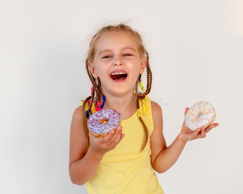 Gullig liten flicka som rymmer två donuts fotografering för bildbyråer