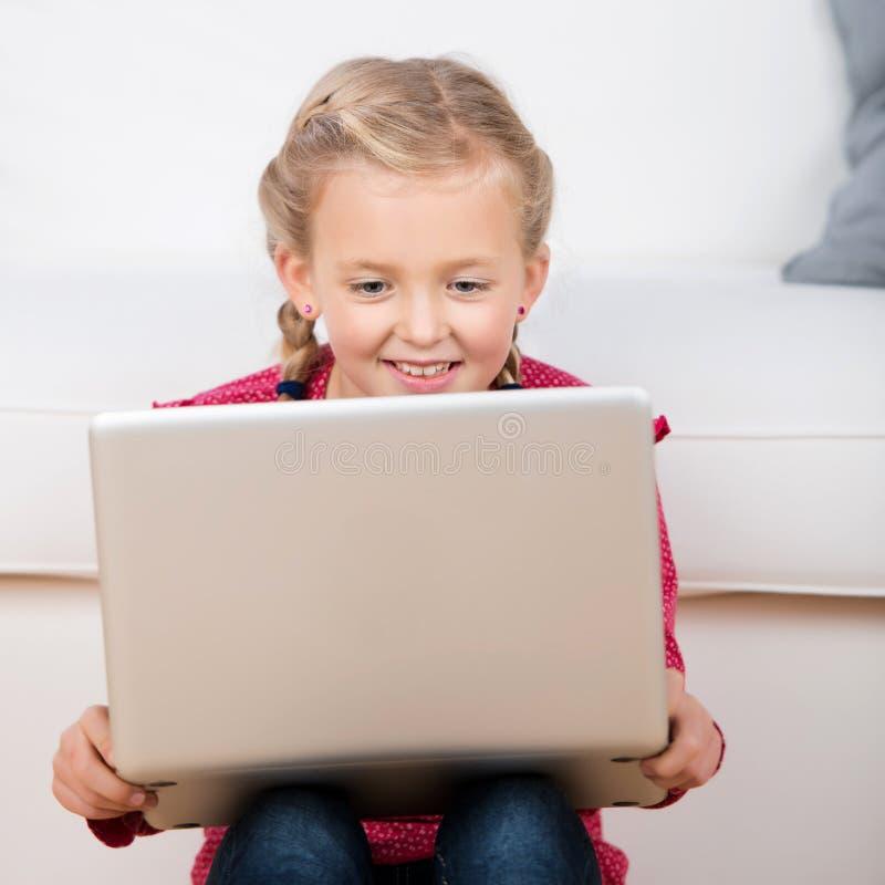 Gullig liten flicka som ser bärbara datorn royaltyfri fotografi