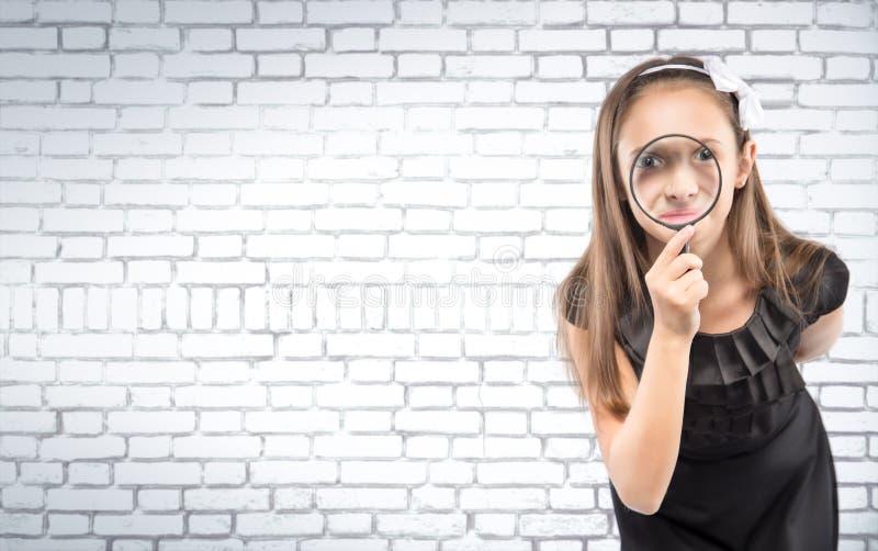 Gullig liten flicka som ser till och med för tegelstenvägg för förstoringsglas en vit bakgrund bilda begrepp royaltyfria foton