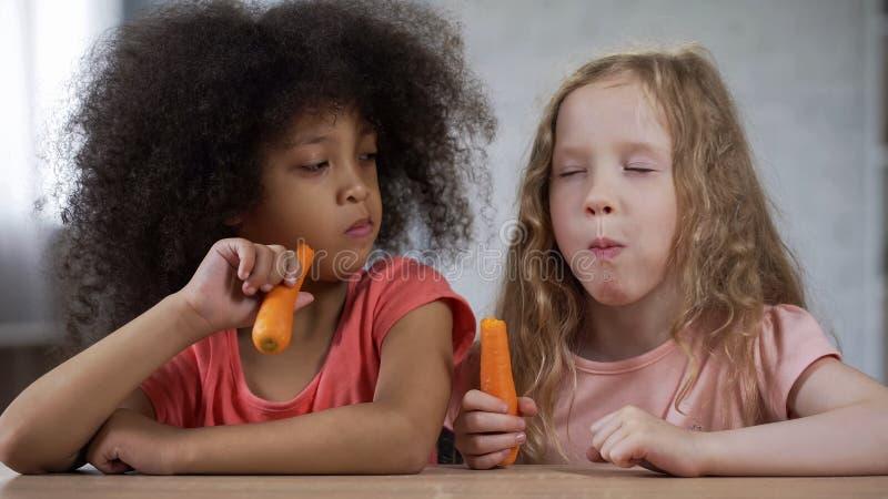 Gullig liten flicka som ser vännen som äter morötter med aptit, sund mat arkivbild