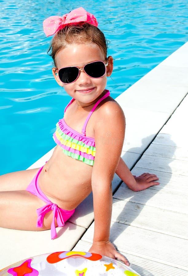 Gullig liten flicka som sitter nära simbassäng arkivbild