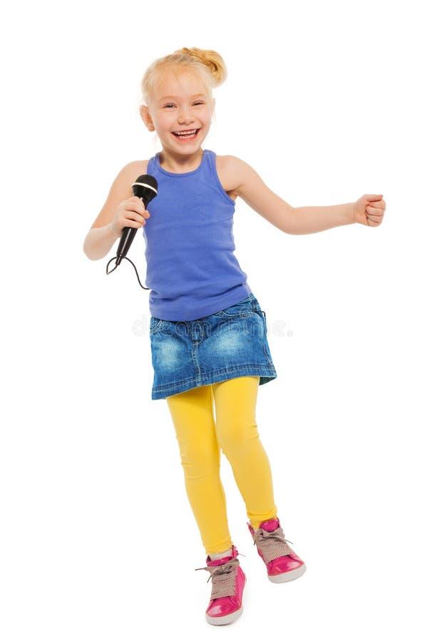 Gullig liten flicka som sjunger, i mikrofon och att dansa royaltyfri fotografi