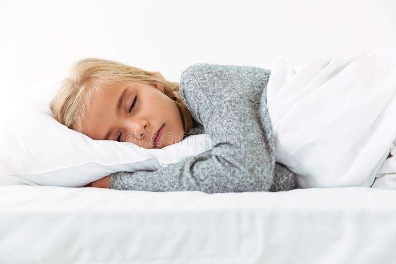 Gullig liten flicka som sover på den vita kudden i grå pyjamashavin arkivfoto