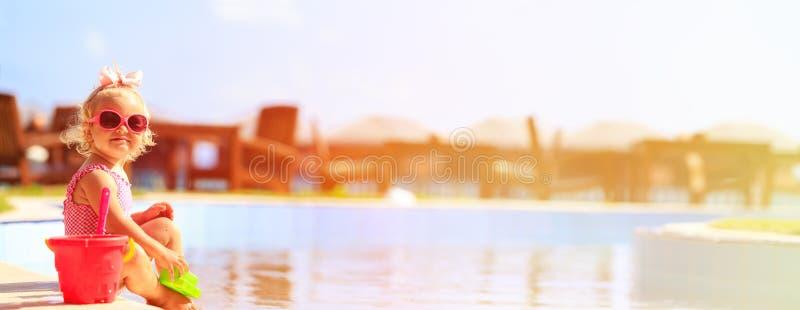 Gullig liten flicka som spelar i simbassäng på stranden fotografering för bildbyråer