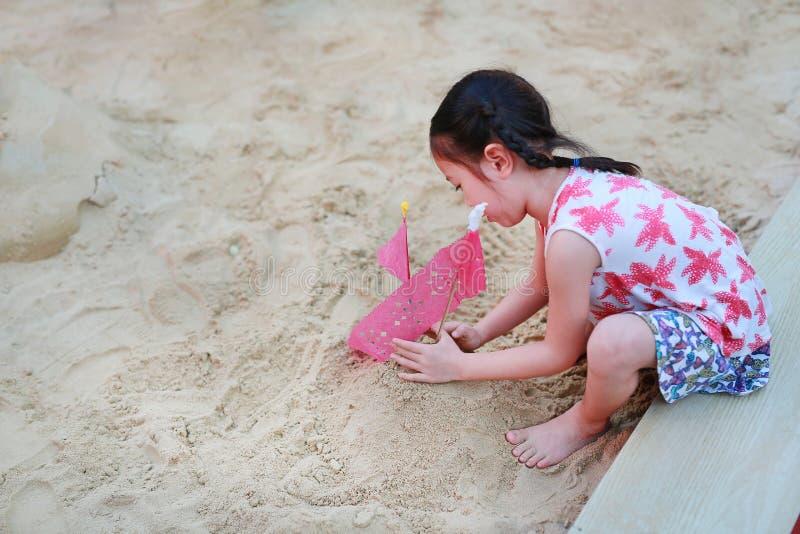 Gullig liten flicka som spelar i trädgård med sand Unge som gör sandslotten under thai kultur fotografering för bildbyråer