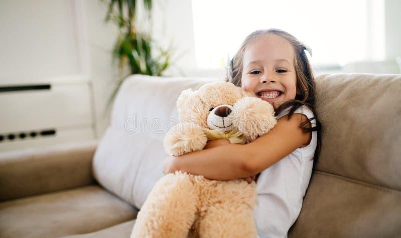 Gullig liten flicka som spelar med nallebjörnen royaltyfri fotografi