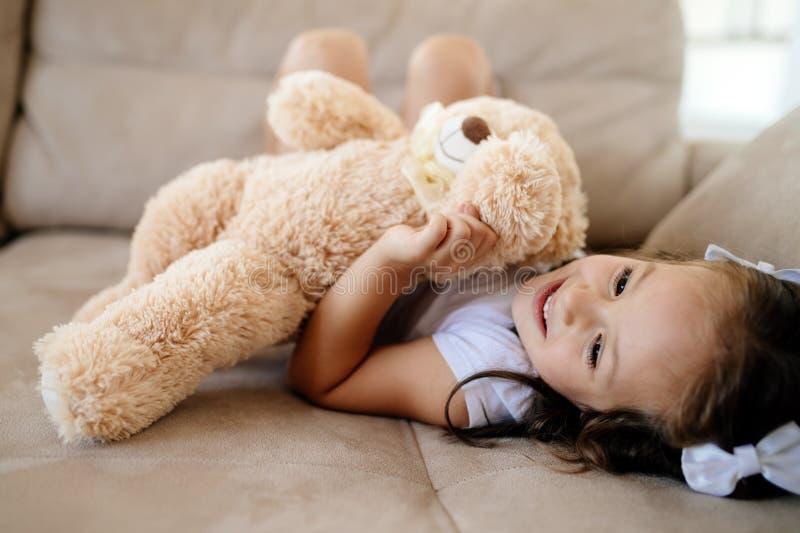 Gullig liten flicka som spelar med nallebjörnen royaltyfria foton