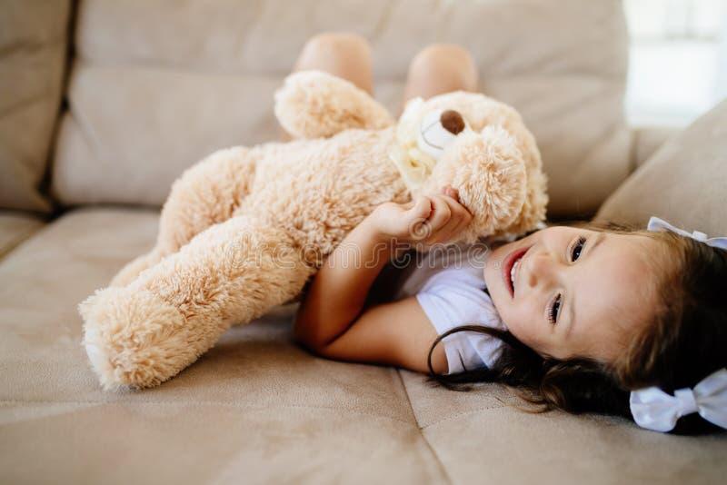 Gullig liten flicka som spelar med nallebjörnen arkivfoto