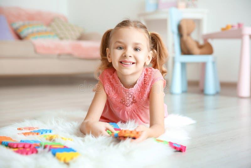 Gullig liten flicka som spelar med pazzles arkivfoton